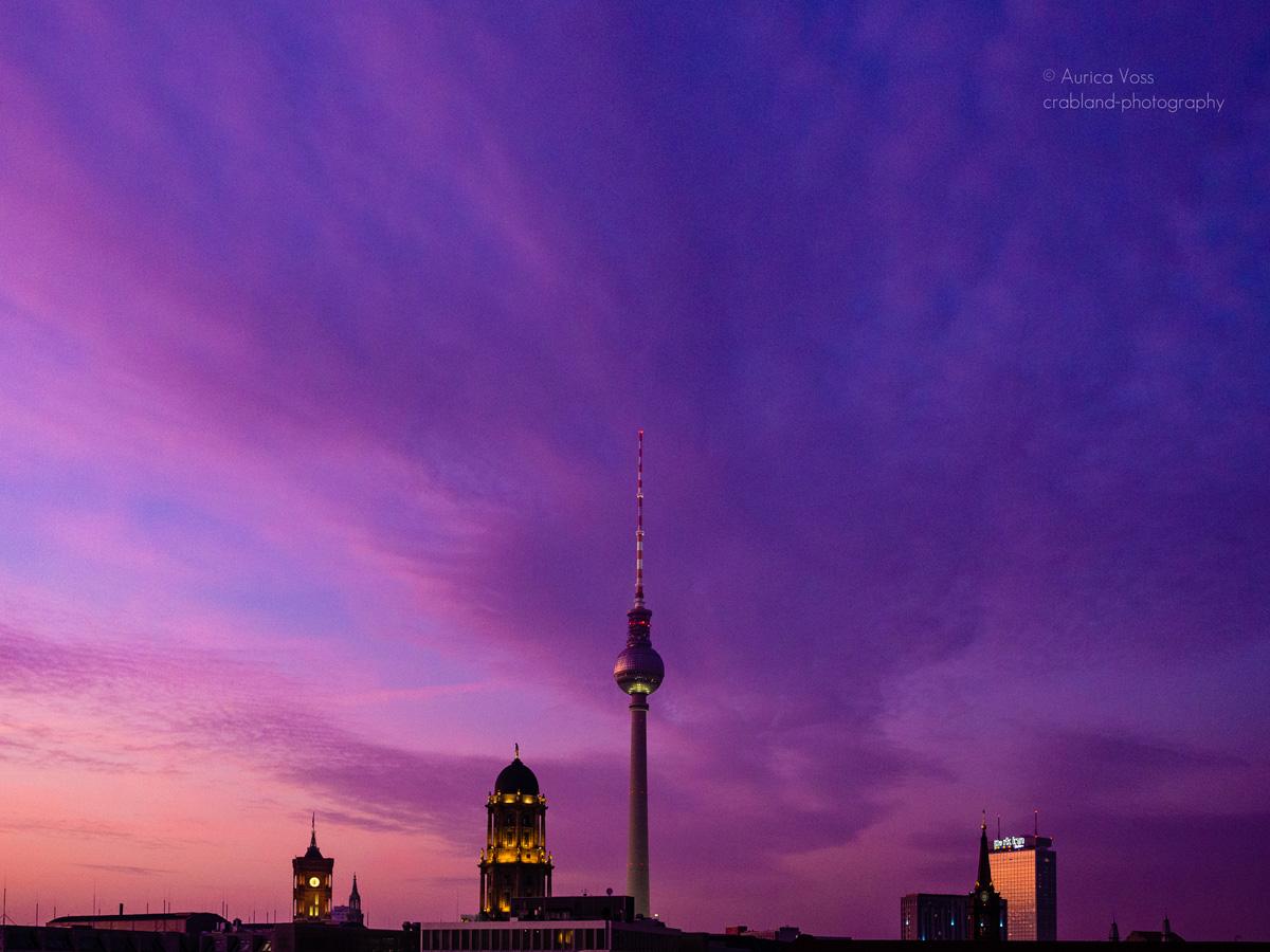 Berliner Fernsehturm und Skyline im Sonnenuntergang mit pinkem Himmel