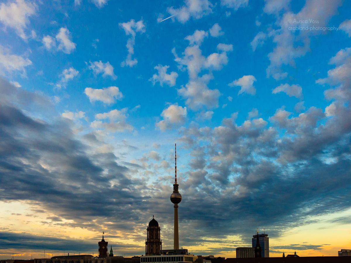 Berliner Fernsehturm und Skyline im Sonnenuntergang. mit Wolken